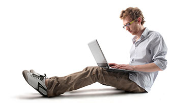 person sitting on ground with a laptop